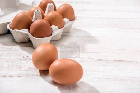 Photo pour Vue rapprochée des oeufs de poulet cru en boîte d'oeufs sur un fond en bois blanc - image libre de droit