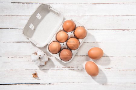 Photo for Top view of raw chicken eggs in egg box on white wooden table - Royalty Free Image