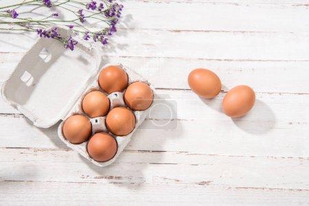 Photo pour Vue du dessus des œufs de poulet crus dans une boîte à œufs ouverte et des petites fleurs violettes sur la table - image libre de droit