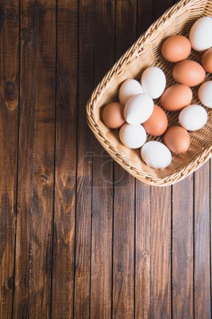 Photo for Top view of raw chicken eggs in basket on table with copy space - Royalty Free Image