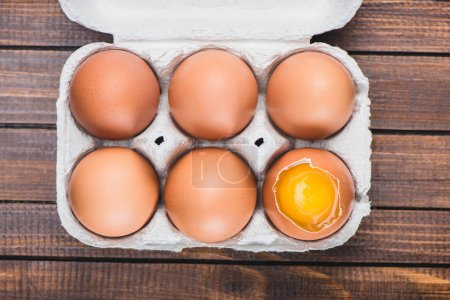Photo for Top view of raw chicken eggs in open carton box on table - Royalty Free Image