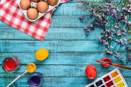 Photo for Top view of colored eggs, paintbrushes and paints for Easter with copy space - Royalty Free Image