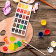 Top view of paints, paintbrushes and palette on ta...