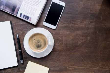 Photo for Top view of coffee cup, smartphone with blank screen, notebook with pen and newspaper on wooden table - Royalty Free Image