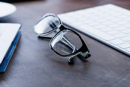 Photo for Close-up view of eyeglasses near keyboard on wooden table - Royalty Free Image