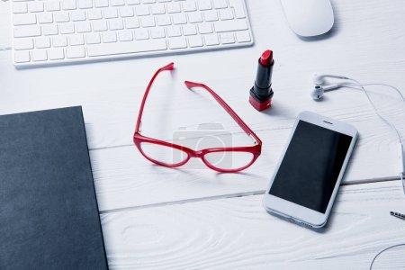 Photo pour Vue de dessus du smartphone, du clavier et des fournitures de beauté sur la table - image libre de droit