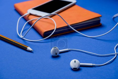 Photo for Side view of smartphone with earphones and notebook on office table - Royalty Free Image