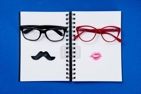 Photo for Top view of pairs of stylish glasses on notebook on blue - Royalty Free Image