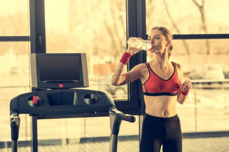 Photo for Young sporty woman drinking water from bottle while standing near trademill in gym - Royalty Free Image
