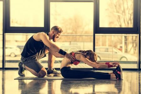 Photo for Side view of smiling bearded trainer helping young woman in stretching - Royalty Free Image