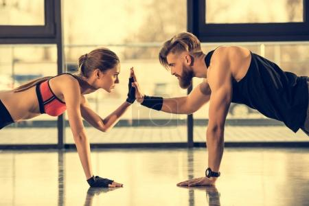 Photo for Young sporty man and woman doing plank exercise and giving high five - Royalty Free Image