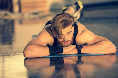 Photo for Young handsome bearded sportsman lying on mat and looking away - Royalty Free Image