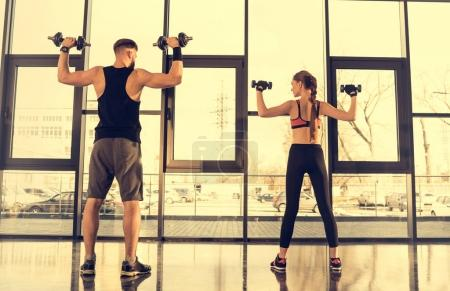 Photo for Back view of sporty man and woman exercising with dumbbells in gym - Royalty Free Image
