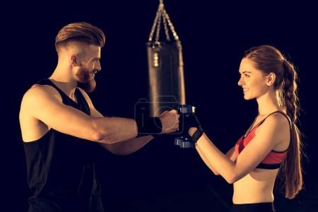 Photo pour Vue latérale de l'homme et de la femme sportifs souriants debout avec des haltères sur noir - image libre de droit