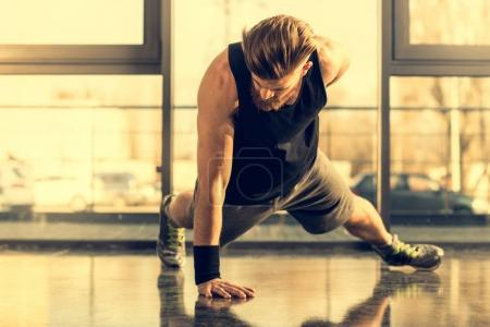 Photo for Young handsome bearded man doing push ups exercise in gym - Royalty Free Image