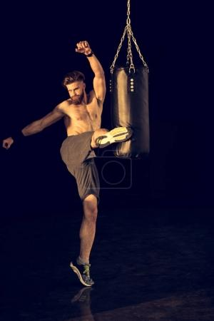 Photo for Young caucasian sportsman kicking punching bag on black - Royalty Free Image