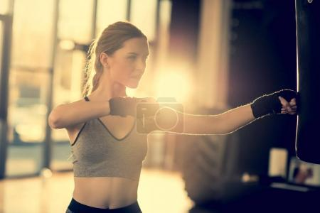 sportswoman with punching bag