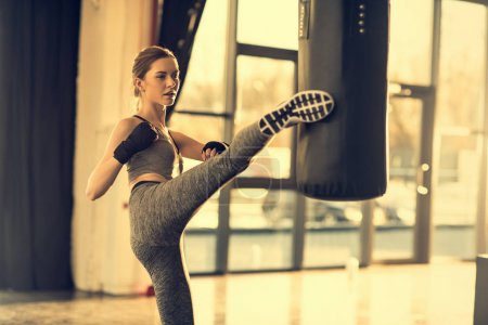 Photo for Young sportswoman kicking punching bag in sports center - Royalty Free Image