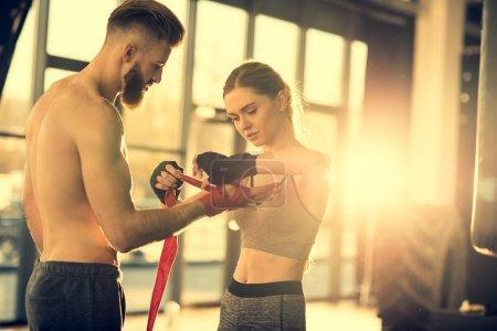Sportswoman wraping man's hand