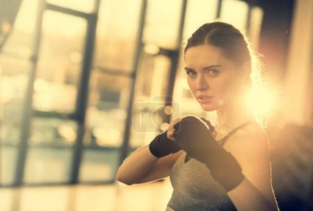 Photo for Sportswoman with wraping hands ready to fight in sports center - Royalty Free Image