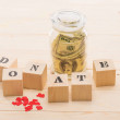 Dollar banknotes in glass jar and wooden cubes wit...
