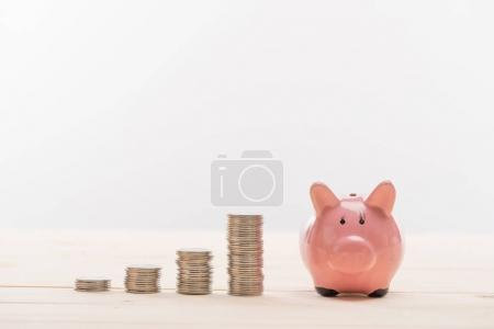 Photo for Close-up view of stacked coins in a row and piggy bank on grey - Royalty Free Image