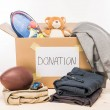 Cardboard box with donation clothes and different ...