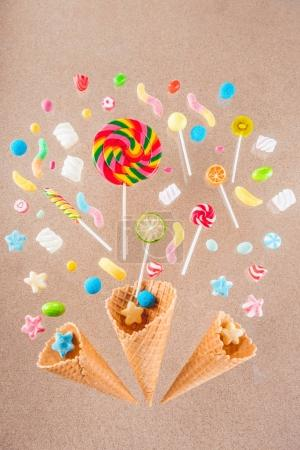 Photo for Close-up top view of crispy waffle cones and mix of sweet candies isolated on beige - Royalty Free Image