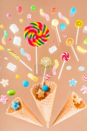 Photo for Close-up top view of crispy waffle cones and mix of colorful sweet candies isolated on beige - Royalty Free Image