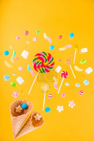 Photo for Close-up top view of waffle cones and mix of various sweets isolated on yellow background - Royalty Free Image
