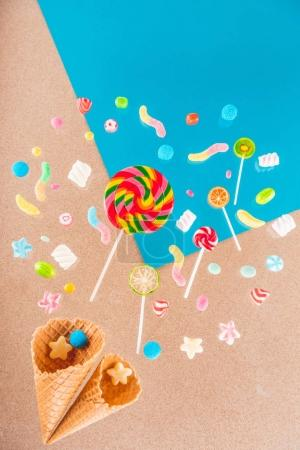 Photo for Close-up top view of tasty crispy waffle cones and different colorful candies isolated on blue and beige - Royalty Free Image