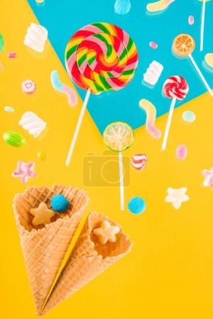 Photo pour Close-up top view of tasty crispy waffle cones and different candies isolated on bright background - image libre de droit