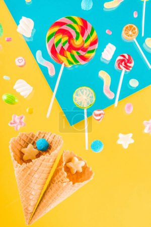 Photo for Close-up top view of tasty crispy waffle cones and different candies isolated on bright background - Royalty Free Image