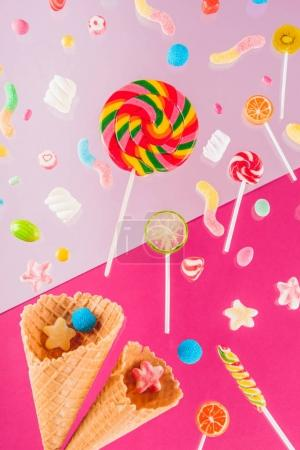 Photo for Close-up top view of tasty crispy waffle cones and different colorful candies isolated on pink - Royalty Free Image