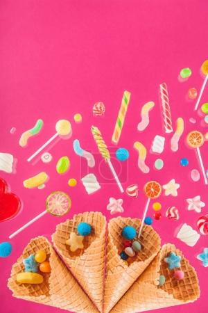 Photo for Close-up top view of waffle cones and mix of various sweets isolated on pink background - Royalty Free Image