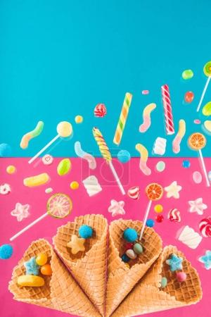 Photo for Close-up view of crispy waffle cones with different gourmet candies isolated on pink and blue - Royalty Free Image