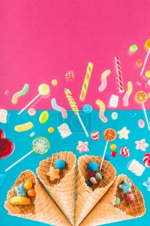 Photo pour Close-up top view of waffle cones and mix of delicious candies isolated on pink and blue - image libre de droit
