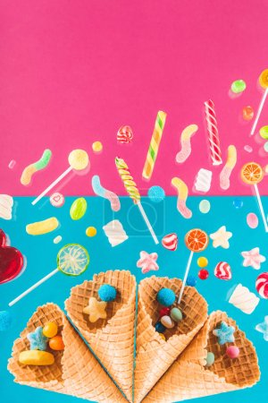 Photo for Close-up top view of waffle cones and mix of delicious candies isolated on pink and blue - Royalty Free Image