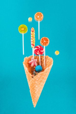 Photo for Close-up view of crispy waffle cone with sweet candies and lollipops isolated on blue - Royalty Free Image