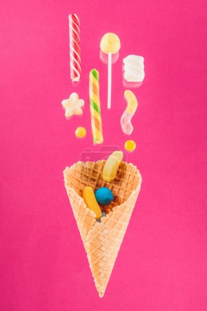 Photo for Close-up top view of tasty crispy waffle cone and mix of delicious sweets isolated on pink - Royalty Free Image