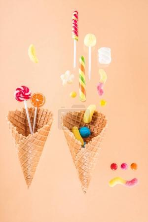 Photo pour Cônes de gaufres avec différents délicieux bonbons à la gelée et sucettes isolées sur beige - image libre de droit