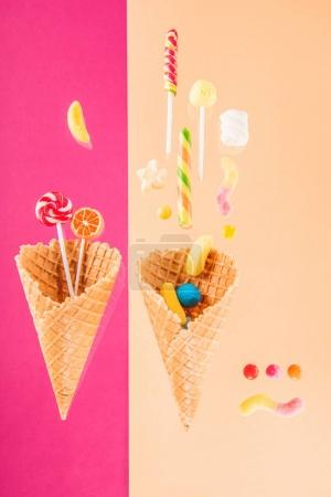 Photo for Waffle cones with different delicious jelly candies and lollipops isolated on pink and beige - Royalty Free Image