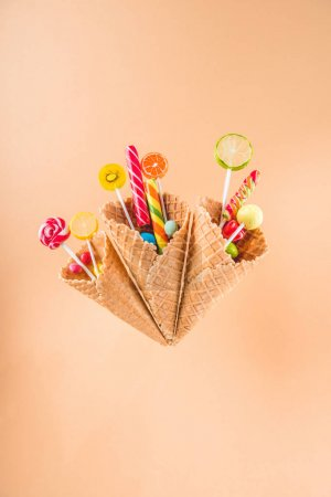 Photo for Waffle cones with different delicious jelly candies and lollipops isolated on beige - Royalty Free Image