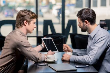 Photo pour Équipe des activités sur la réunion sur le projet avec tablette numérique en café, concept de déjeuner d'affaires - image libre de droit