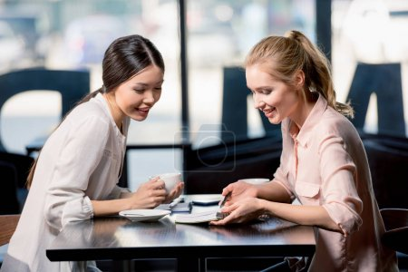 Young women drinking coffee and discussing