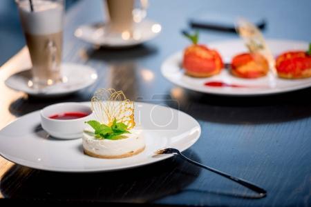Photo pour Bouchent la vue de savoureux desserts avec des tasses à café sur la table dans le restaurant - image libre de droit