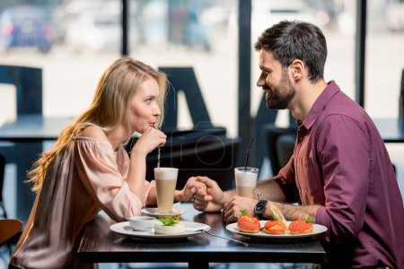 Photo for Side view of couple in love having lunch together in restaurant - Royalty Free Image