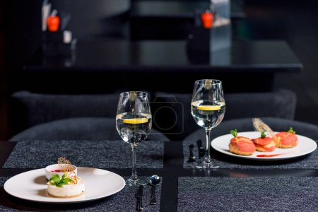 Photo for Close up view of tasty desserts and glasses of water on table in restaurant - Royalty Free Image