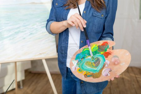 Photo for Partial view of woman artist holding paintbrush and palette while painting picture - Royalty Free Image