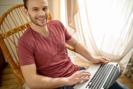 Man with laptop in rocking chair